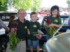 Market manager Ray Satterfield and Grand children display fresh produce for sale.